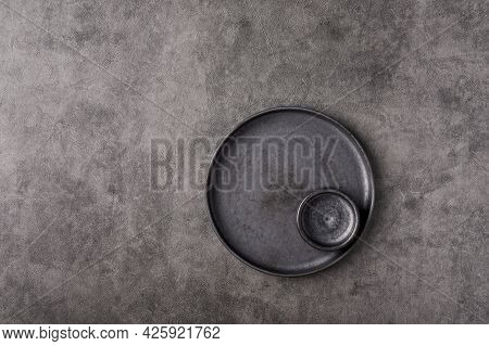 Empty Dark Plate With Saucer Set On Gray Graphite Textured Background. Top View, Copy Space