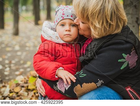 Mature Mom With Baby Girl At Park, Walk And Having Fun, Late Motherhood After 40 Years
