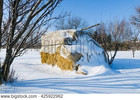 Rural Winter Background With Big Square Stack Of Dry Yellow Hay Covered By Plastic And Heavy Snow At