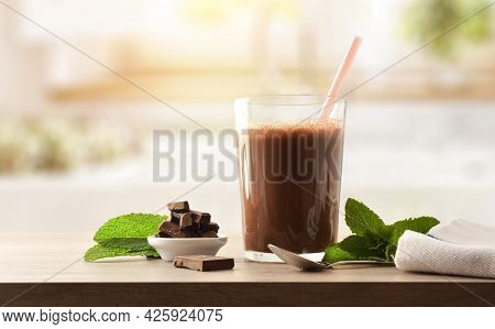 Glass With Milk Chocolate Shake With Chocolate Portions On Wooden Bench In Kitchen. Front View.