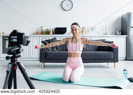 Sportive Woman Training With Dumbbells Near Blurred Digital Camera At Home.