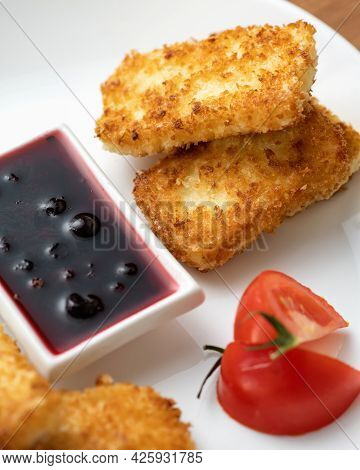 Pieces Of Cheese Fried In Breadcrumbs. Berry Sauce And Tomato On White Plate. Close-up Shot. Vertica