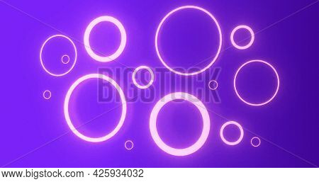 Pulsating pink neon rings in various sizes glowing on purple background. energy, electricity, luminosity, colour and movement concept, digitally generated image.