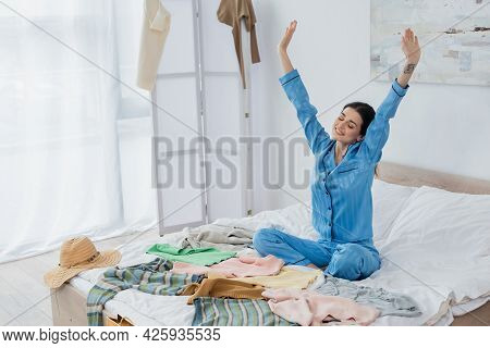 Joyful Woman In Silk Pajama Stretching On Bed Near Plenty Of Different Clothes.