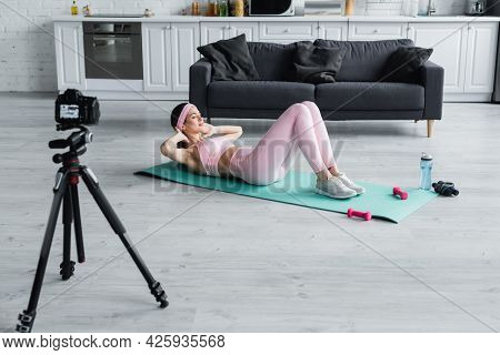 Sportive Woman Doing Abs Exercise Near Dumbbells, Sports Bottle And Digital Camera.