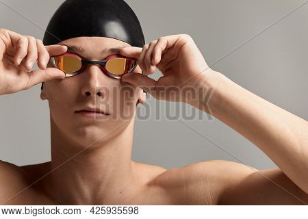 Swimmer In A Cap And Mask, On A Gray Background, Preparing To Swim, Close-up, Advertising Banner For