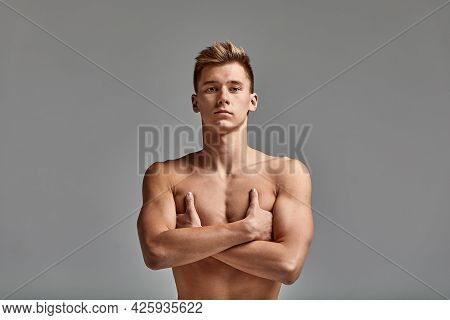A Male Swimmer Stands With Crossed Arms, Against A Gray Background.