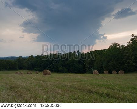 Rural Landscape With Rolls Of Hay, Meadow And Roll Bales During Overcast Stormy Summer Day