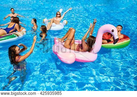Friends Having Party In Private Holiday Villa Swimming Pool. Happy Young People Swim On Inflatable F