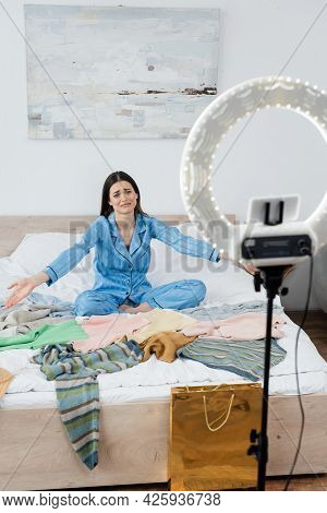 Displeased Woman In Trendy Pajama Pointing At Plenty Of Clothes Near Phone Holder With Circle Light.
