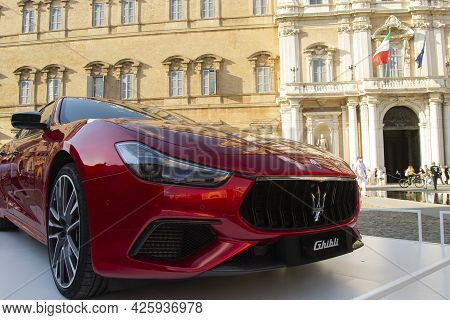 01-07-2021, Modena - Italy. Motor Valley Cars Exibition, Red Maserati Ghibli In Front Of Italian Arm