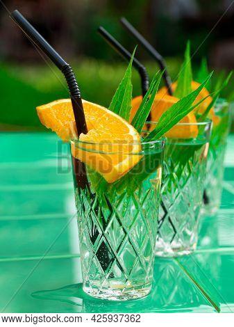 Refreshing Drinks In Crystal Glasses With Leaves Orange Slice Green Tile Background Shadows. Sweet C
