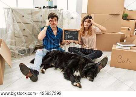 Young caucasian couple with dog holding our first home blackboard at new house worried and stressed about a problem with hand on forehead, nervous and anxious for crisis