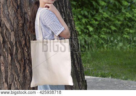 Empty Reusable Canvas Tote Bag Mockup. Natural Canvas Eco-friendly Shopper Bag On Girl's Shoulder. M
