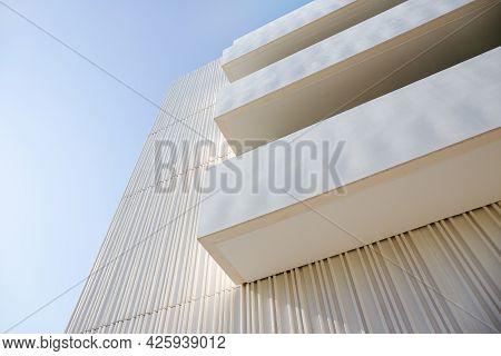 Low Angle View Of Balconies On A Modern Building Facade. Decorative White Concrete Facade. Copy Spac