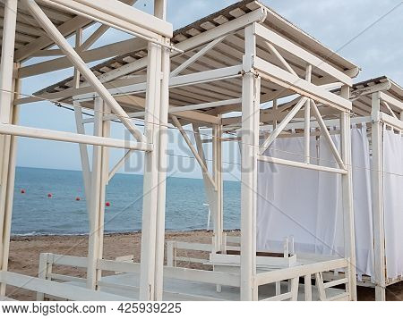 An Umbrella For Sunbathing On The Beach. Bungalows For Summer Holidays On The Sand