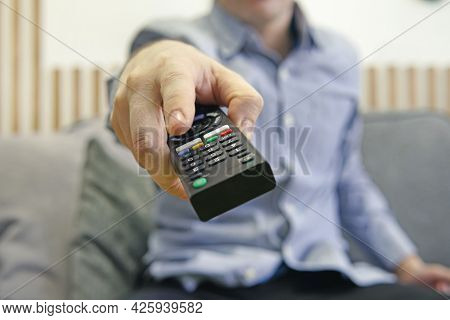 The Man With The Remote Control In Hand Watching The Sports Channel And Presses The Button On The Re