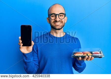 Young hispanic man holding take away food showing smartphone screen smiling with a happy and cool smile on face. showing teeth.