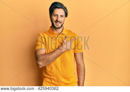Young hispanic man wearing casual yellow t shirt cheerful with a smile of face pointing with hand and finger up to the side with happy and natural expression on face