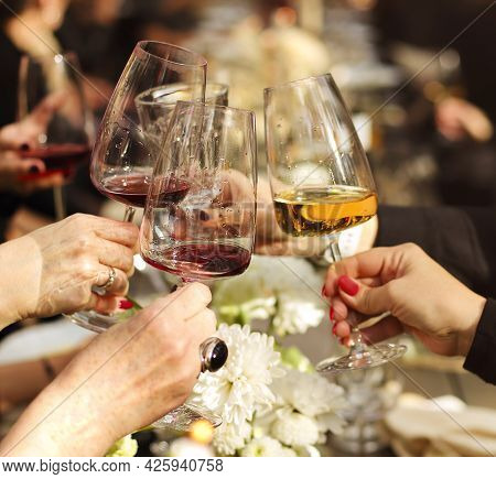 Group Of Crop Anonymous Friends Clinking Glasses With Wine While Gathering Around Table With Delicio