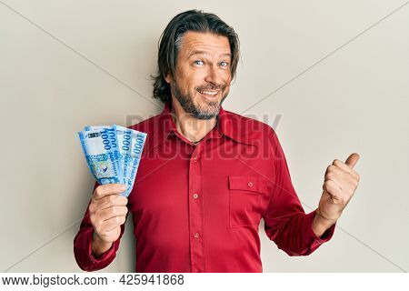 Middle age handsome man holding 1000 hungarian forint banknotes pointing thumb up to the side smiling happy with open mouth