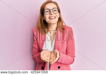 Young caucasian woman wearing business style and glasses smiling with hands palms together receiving or giving gesture. hold and protection