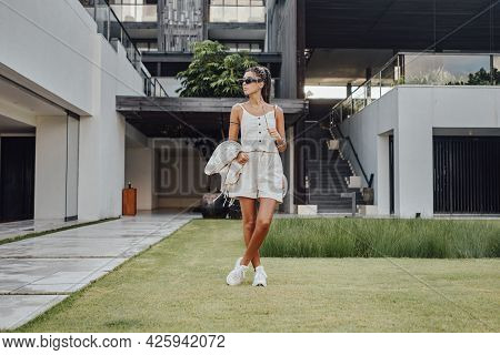 Happy Woman With Sunglasses On Lawn Against Mansion