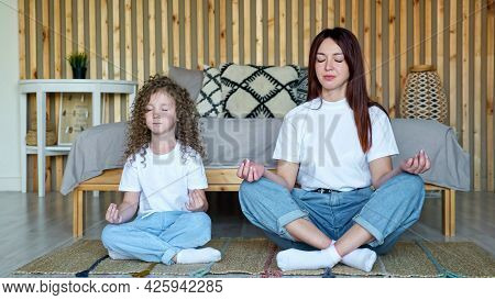 Little Girl With Loose Hair And Mother In White T-shirts And Blue Denim Jeans Sit In Yoga Poses Medi