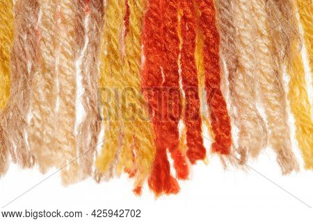 fringed edge of a small handmade rug or mat, woven from red and yellow wool threads, one object close-up