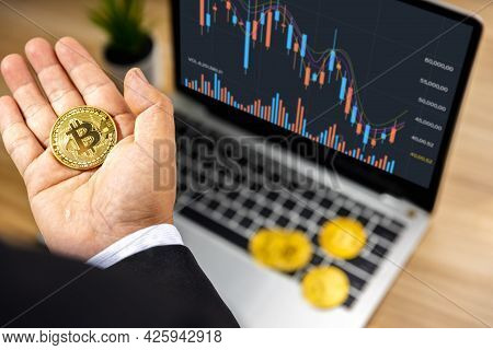 Business Bitcoin On Hand Of Investor With Graph Chart On Laptop On Wood Table, Stock Market And Fore