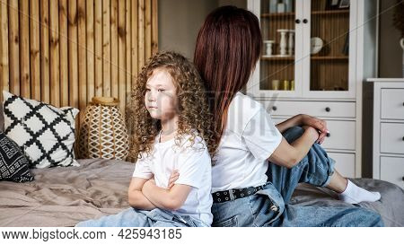 Angry Little Girl With Long Loose Curly Hair Crosses Hands Sitting Back To Brunette Mother On Grey B