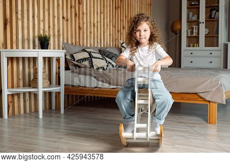 Cute Preschooler Girl With Long Loose Curly Brown Hair Sits On White Wooden Rocking Horse And Rocks