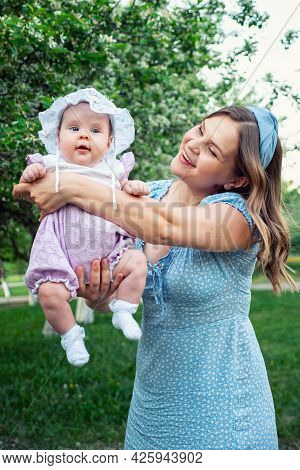 Young Woman With Loose Fair Hair Rocks In Arms Baby Girl And Plays With Kid Standing In Park Against