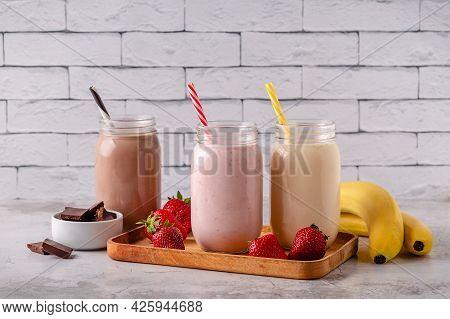 Set Of Strawberry Banana And Chocolate Milkshakes In The Glass Jars