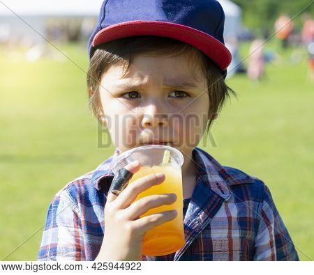 High Key Portrait Of Kid Boy Drinking Orange Slush From Plastic Glass In Hot Sunny Day,thirsty Child