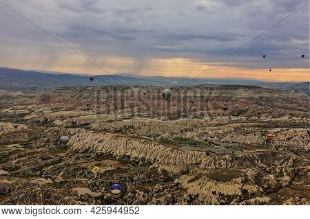 Colorful Balloons Fly Over Cappadocia At Sunrise. In The Valley There Are Quaint Mountains With Shar