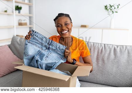 Happy Black Woman Holding Jeans, Unboxing Cardboard Package, Receiving Ordered Product, Satisfied Wi