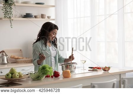 Pretty Housewife Tasting Fresh Meal At Home. Chef Taste Food, Cook, Covid-19