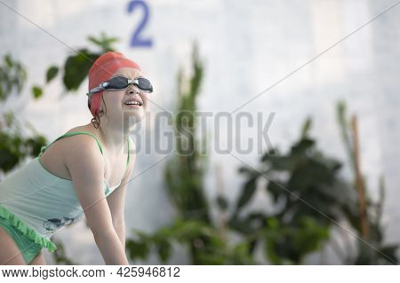 A Girl In A Swimsuit And A Swimming Cap With Glasses In The Sports Pool.