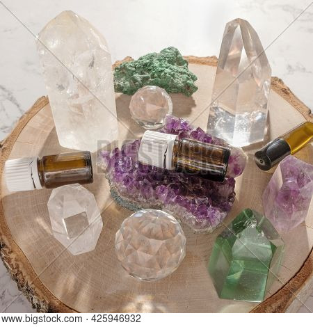 Essential Oil Glass Bottles, Beautiful Crystals And Gemstones On Wooden Log Slice. Healing Minerals