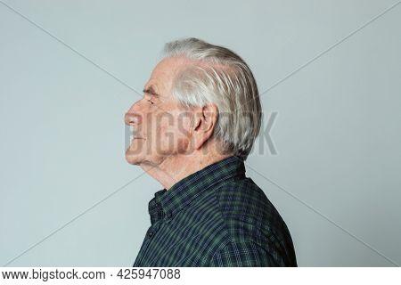 Senior man wearing a tartan shirt in profile shot