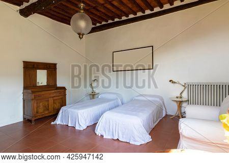 Interior of a bedroom with two single beds. Spartan ambiance and nothing luxurious. There are no people inside and the floors are red and beautiful.