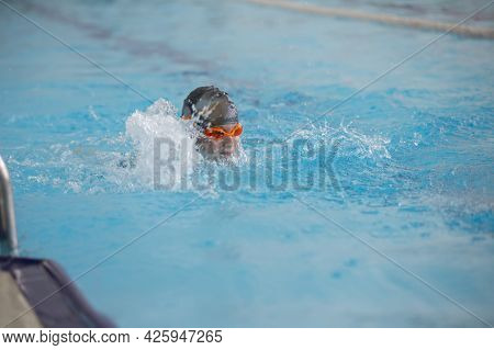 A Boy In A Swimming Cap And Glasses Is Swimming In The Sports Pool.