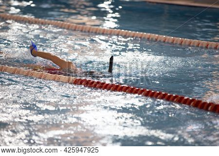 Child Athlete Swims In The Pool. Swimming Section.