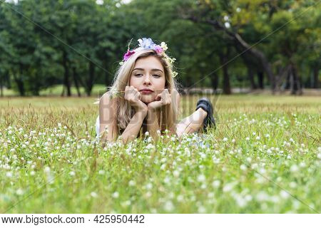 Enjoyment Young Woman With Flower On Her Hair Blowing On Dandelion Flowers While Lying On Green Gras