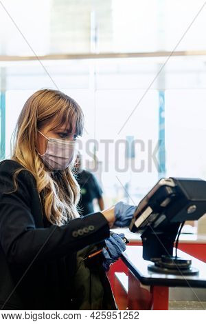 Woman in a face mask wearing latex gloves while purchasing at a self-checkout in a supermarket during coronavirus quarantine