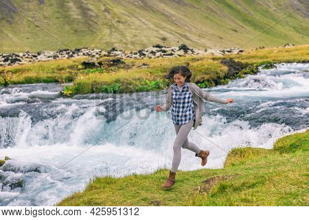 Woman joyful cheerful happy aspirational joyous smiling laughing having fun by waterfall on Iceland. Girl tourist in casual clothing visiting icelandic nature landscape.