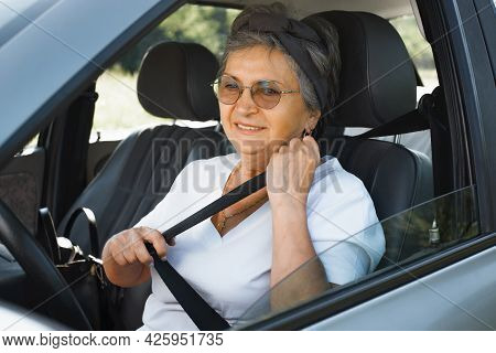 Mature Smiling Woman With Glasses Sitting In Car Behind The Wheel And Wearing Seat Belt. Senior Woma