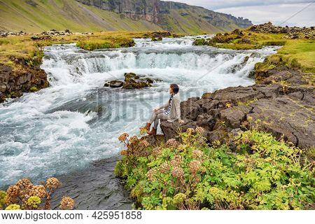 Woman sitting by waterfall on Iceland. Girl tourist visiting amazing icelandic nature landscape.