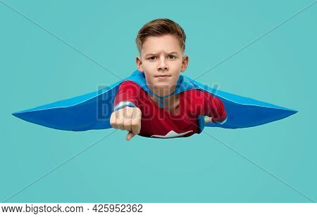 Serious Boy In Superhero Costume Flying With Clenched Fist Ready For Help On Blue Background